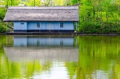 Nabrzeże drewniany dom z pokrywającym strzechą dachem Malujący w błękicie obraz stock