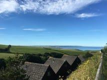 Nabrzeżna ziemia uprawna z jasnym niebem widzieć od wioski zdjęcie stock
