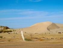 Nabrzeżne piasek diuny z opona śladami i drut kolczasty one fechtują się przeciw niebieskiemu niebu w Libia fotografia stock