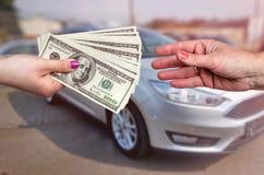 Nabywać samochód, dolarowi banknoty w żeńskich rękach zdjęcie royalty free