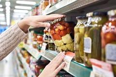 Nabywc ręki z słojem soleni pomidory i kabaczek w sklepie Obraz Stock