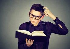 Nach dem Ablesen eines Buches verwirrter Mann in den Gläsern verdutzte stockbild