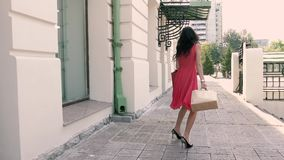 Nach dem Einkauf glückliche junge Frau geht hinunter die Straße stock video footage