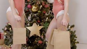 Nach dem Einkauf zwei sexy Frauen in der Unterwäsche sind Stand am Weihnachtsbaum mit Taschen stock footage
