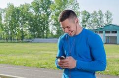 , nach der Ausbildung, ein junger Athlet schreibt eine Mitteilung auf den Smartphone und hört Musik stockfotografie