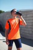 Nach der Ausbildung tragen Sie, Eignung - junge Läufermanngetränke von einer Flasche das Wasser oder ein Proteindrink, männlicher Lizenzfreies Stockfoto