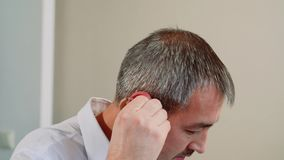 Nach der Ausstattung ein Mann entfernt ein Hörgerät stock footage