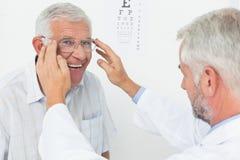 Nach der Durchführung des Sehtests an Doktor bemannen Sie tragende Gläser stockfoto