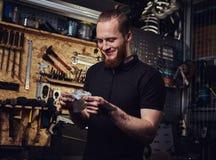 Nach der Reparatur des Arbeitens in einer Werkstatt hübsche lächelnde Rothaarigearbeitskraft, seine schmutzigen Hände säubernd Lizenzfreie Stockfotos