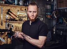 Nach der Reparatur des Arbeitens in einer Werkstatt hübsche stilvolle Rothaarigearbeitskraft, seine schmutzigen Hände säubernd Lizenzfreies Stockfoto
