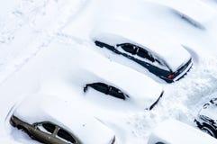 Nach einem Schneesturm werden Autos im Parkplatz mit einem Th bedeckt Lizenzfreies Stockfoto