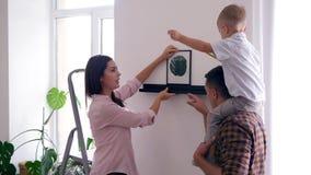 Nach Hause neu streichend, hängen junge Paare mit kleinem Jungen Malerei auf Wand während der Erneuerung in der Wohnung stock footage