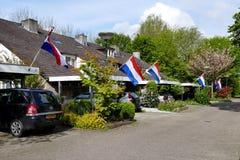 Nachbarschaft in einem niederländischen Dorf mit der niederländischen Flagge auf kingsday Stockfoto
