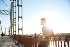 Nachdem dem Laufen trägt den Mann zur Schau, der, beim Lehnen am Brückengeländer stillsteht Lizenzfreie Stockfotografie