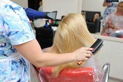 Nachdem er Haar gefärbt hat, wäscht der Friseur das Mädchen ` s Haar und das wa Lizenzfreies Stockfoto