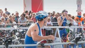 Nachdem sie das Wasser herausgenommen haben, nehmen Athleten ihr laufendes Fahrrad Stockbild