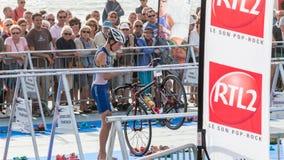 Nachdem sie das Wasser herausgenommen haben, nehmen Athleten ihr laufendes Fahrrad Lizenzfreies Stockbild