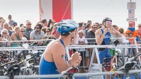 Nachdem sie das Wasser herausgenommen haben, nehmen Athleten ihr laufendes Fahrrad Lizenzfreie Stockbilder