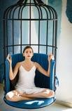 Nachdenklich und ruhig Nettes Frauenkonzentrat und im Stuhl meditieren Frau entspannen sich in Lotussitz zu Hause recht lizenzfreie stockbilder