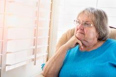 Nachdenkliche ältere Frau, die aus ihrem Fenster heraus anstarrt Stockfoto