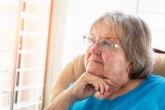 Nachdenkliche ältere Frau, die aus ihrem Fenster heraus anstarrt Lizenzfreies Stockfoto