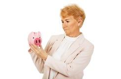 Nachdenkliche ältere Frau, die Sparschwein hält Stockbilder