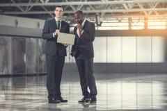 Nachdenkliche Arbeitgeber, die mit Gerät arbeiten stockfotografie