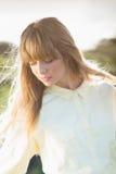 Nachdenkliche attraktive blonde Aufstellung in der Landschaft Lizenzfreies Stockbild