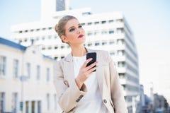 Nachdenkliche attraktive Geschäftsfrau, die eine Textnachricht sendet Lizenzfreie Stockfotos