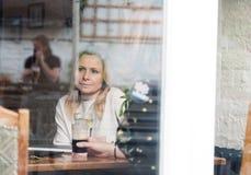 Nachdenkliche blonde attraktive junge erwachsene allein stehende Frau in der Kneipe Lizenzfreie Stockbilder