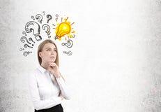 Nachdenkliche blonde Frau, Birne und Fragen, konkret Lizenzfreies Stockbild