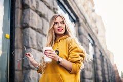 Nachdenkliche blonde Frau, die auf modernen Straßen, trinkendem Kaffee oder Cappuccino Straßenmodekonzept, junge Frau tragendes b Stockfoto