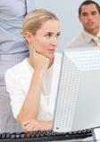 Nachdenkliche blonde Frau, die an einem Computer arbeitet Lizenzfreie Stockfotos
