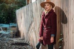 Nachdenkliche blonde Frau, die mit dem Geldbeutel im Freien steht Stockfotografie