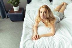 Nachdenkliche blonde Frau, die zu Hause auf Bett liegt Stockbild