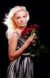 Nachdenkliche blonde Frau mit Bündel Lizenzfreie Stockbilder