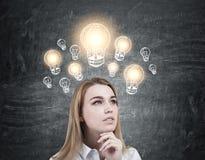 Nachdenkliche blonde Frau und glänzende Glühlampen Stockbilder