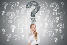 Nachdenkliche blonde Frau und viele Fragen Stockbilder