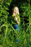 Nachdenkliche Blondine im Wald Stockfotos