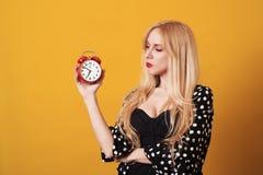 Nachdenkliche blondy Frau, die Wecker über gelbem Hintergrund betrachtet lizenzfreies stockfoto