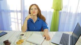 Nachdenkliche braunhaarige Frau in einem Café an einem Tisch schreibt in das Tagebuch stock footage