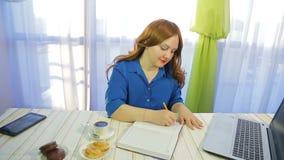 Nachdenkliche braunhaarige Frau in einem Caf? an einem Tisch schreibt in das Tagebuch stock footage