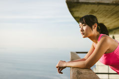 Nachdenkliche Eignungsfrau, die den Ozean schaut Stockbilder