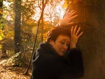 Nachdenkliche erwachsene Frau im sonnigen Wald des Herbstes emotional Stockfoto
