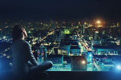 Nachdenkliche Frau betrachtet Nachtstadt Lizenzfreie Stockfotos