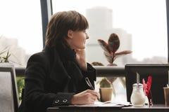 Nachdenkliche Frau in der schwarzen Funktion im Kaffee lizenzfreie stockfotos