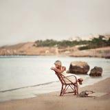 Nachdenkliche Frau, die auf den Dünen sitzt Lizenzfreies Stockbild