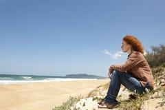 Nachdenkliche Frau, die auf den Dünen sitzt Lizenzfreie Stockbilder