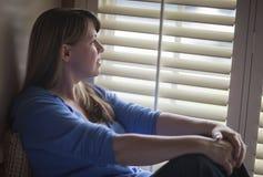 Nachdenkliche Frau, die nahe Jalousien sitzt Stockbilder