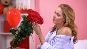 Nachdenkliche Frau, die Rosen vom stillen Bewunderer am Valentinsgrußtag, Überraschung hält lizenzfreie stockbilder